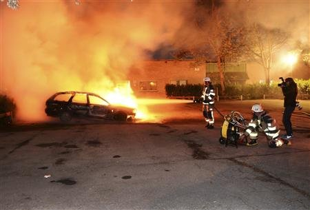 Firefighters responding to rioting in the suburbs of Stockholm, Sweden. Image by Scanpix.