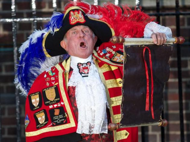 A town crier announces the arrival of the youngest member of the British royal family outside St. Mary's Hospital in Paddington, West London. Image from AFP.