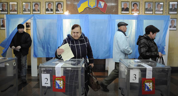 A Crimean woman casts her vote. Yesterday, Crimean authorities announced that voters had overwhelmingly chosen to leave Ukraine and join Russia. Image by Andrew Lubimov of the AP.